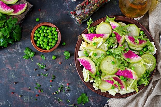 Sałatka z liści rzodkiewki, ogórka i sałaty. wegańskie jedzenie. menu dietetyczne. widok z góry. leżał płasko