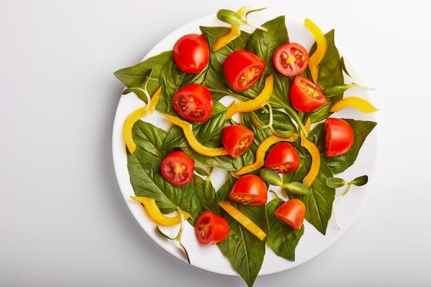 Sałatka z liśćmi bazylii, pomidorami cherry i papryką na białym talerzu. widok z góry