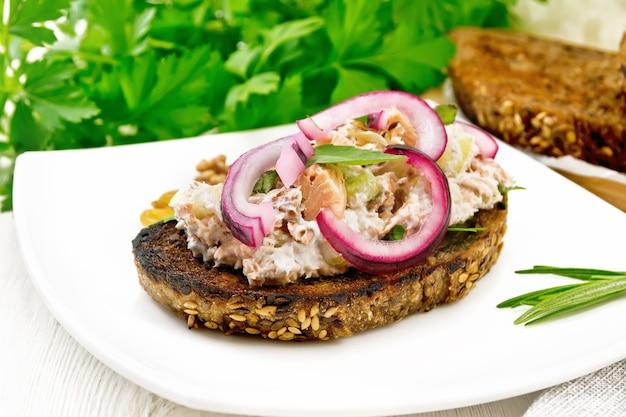 Sałatka z łososia, seler naciowy, rodzynki, orzechy włoskie, czerwona cebula i twarożek na tostowym chlebie z zieloną sałatą na talerzu na tle drewnianej deski