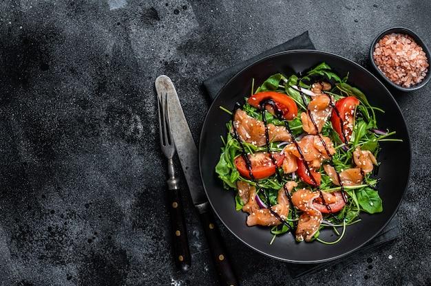 Sałatka z łososia z plastrami ryb, rukolą, pomidorem i zielonymi warzywami