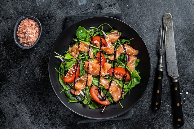 Sałatka z łososia z plastrami ryby, rukolą, pomidorem i zielonymi warzywami. czarny stół. widok z góry.