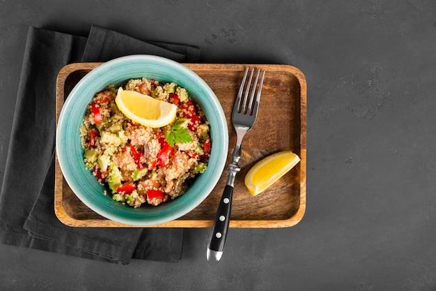 Sałatka z łososia z pomidorami, awokado i komosą ryżową w niebieskiej misce