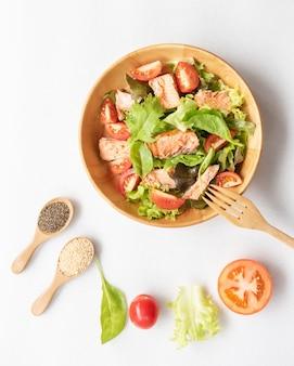 Sałatka z łososia z pomidorkami koktajlowymi, domowe jedzenie. pomysł na smaczny i zdrowy posiłek. drewniana miska na białym tle.
