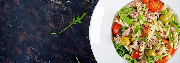 Sałatka z makaronem z tuńczykiem, pomidorami, oliwkami, ogórkiem, słodką papryką i rukolą na rustykalnym tle. transparent. widok z góry