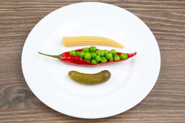 Sałatka z marynowanej kukurydzy, groszku, ogórka i czerwonej papryki na białym talerzu