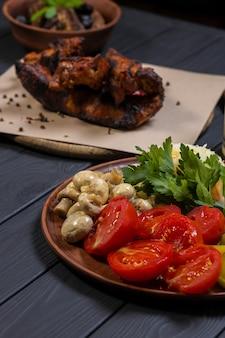 Sałatka z marynowanych warzyw i bimber na czarnym tle drewnianych