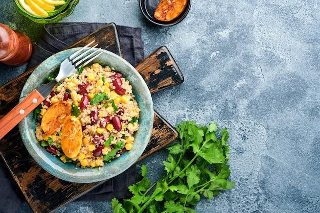 Sałatka z meksykańskiej czarnej fasoli z quinoa z karmelizowaną cytryną w starej glinianej misce vintage na ciemnoszarym betonowym tle. tradycyjne danie kuchni meksykańskiej. widok z góry,