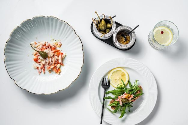 Sałatka z mięsem kraba na kuchennym stole. białe tło. widok z góry.