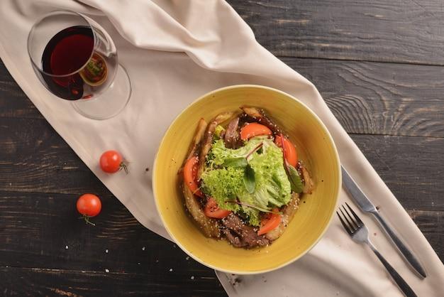 Sałatka z mięsem, pomidorami, sezamem i sałatą. w żółtym talerzu na drewnianym stole