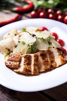 Sałatka z mięsem, serem i pomidorami na drewnianym stole