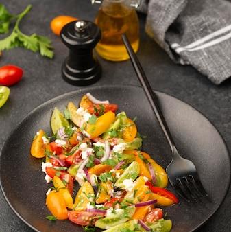 Sałatka z mieszanki pomidorów pod wysokim kątem z serem feta, rukolą i widelcem