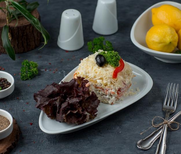 Sałatka z mimozy w porcjach z ziemniakami, marchewką, kurczakiem, białkiem jaja, serem holenderskim