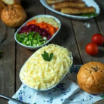 Sałatka z mimozy z widokiem z boku z chlebem i pomidorami