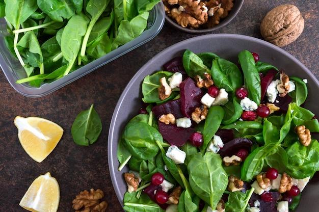 Sałatka z młodym szpinakiem, gotowanymi burakami, serem pleśniowym, orzechami, żurawiną w misce. danie fitness smaczne diety. sałatka witaminowa odpowiednie odżywianie. widok z góry.