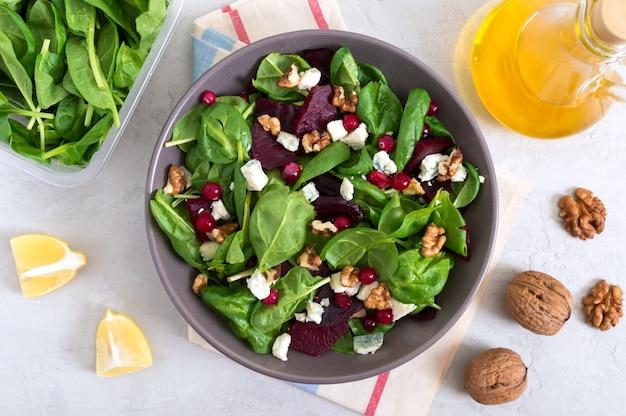 Sałatka z młodym szpinakiem, gotowanymi burakami, serem pleśniowym, orzechami, żurawiną w misce na lekkiej powierzchni. danie fitness smaczne diety. sałatka witaminowa odpowiednie odżywianie. widok z góry.
