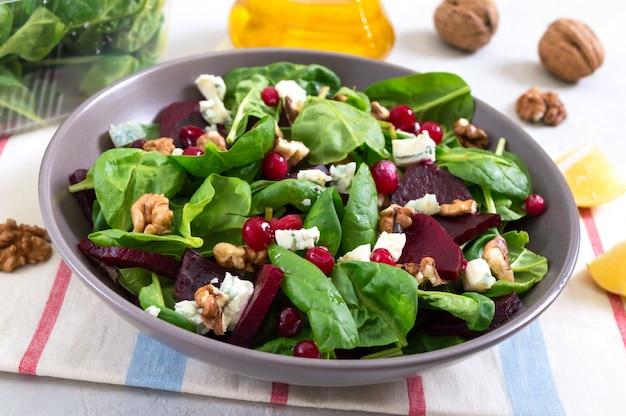 Sałatka z młodym szpinakiem, gotowanymi burakami, serem pleśniowym, orzechami, żurawiną w misce na lekkiej powierzchni. danie fitness smaczne diety. sałatka witaminowa odpowiednie odżywianie