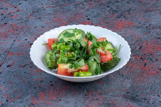 Sałatka z ogórków i pomidorów zmieszana z natką pietruszki na ciemnym tle. zdjęcie wysokiej jakości