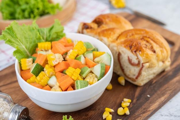 Sałatka z ogórków, kukurydzy, marchwi i sałaty w białej filiżance.