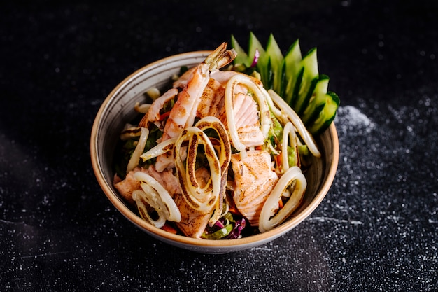 Sałatka z owoców morza z filetem z łososia, krabami i warzywami w misce.