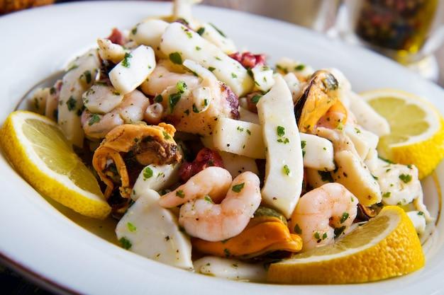 Sałatka z owoców morza z krewetkami, małżami, kalmarami, ośmiornicą udekorowaną pietruszką