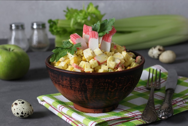 Sałatka z paluszkami krabowymi, selerem, jabłkiem i jajkami przepiórczymi w ciemnej misce na szarym tle. zdrowe odżywianie.