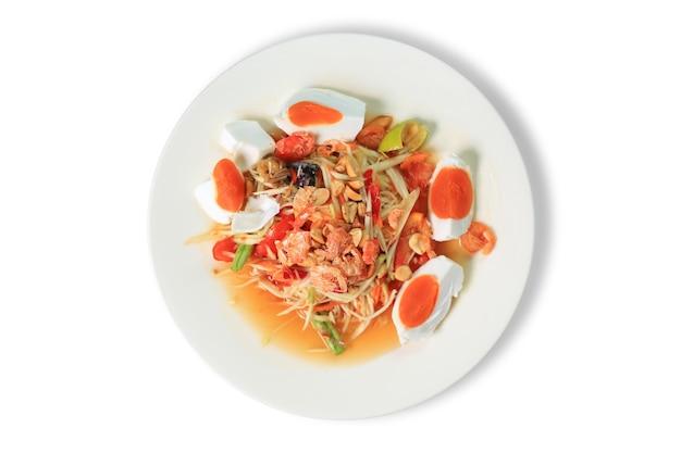 Sałatka z papai (som tam) z solonym jajkiem i krewetkami tradycyjne tajskie potrawy na białym tle. najbardziej poszukiwane popularne jedzenie w tajlandii. widok z góry