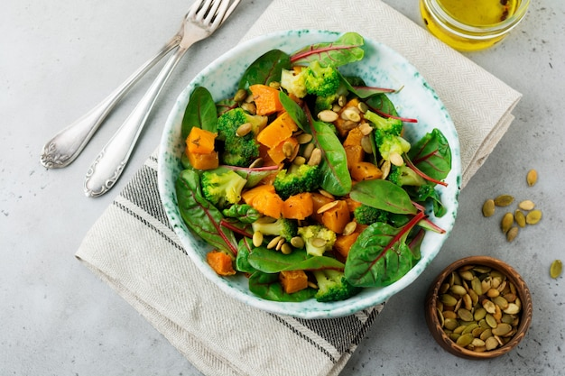 Sałatka z pieczoną dynią, boćwiną, brokułami i pestkami dyni na talerzu ceramicznym na kamiennym lub betonowym stole. styl rustykalny.