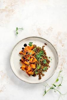 Sałatka z pieczoną dynią, soczewicą i dressingiem balsamicznym ozdobiona groszkową mikrozielenią na jasnym tle. zdrowe wegańskie jedzenie, widok z góry