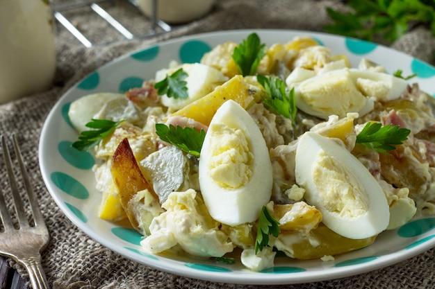 Sałatka z pieczonymi ziemniakami jajko z ogórka kiszonego i wędzonym indykiem na stole w stylu rustykalnym