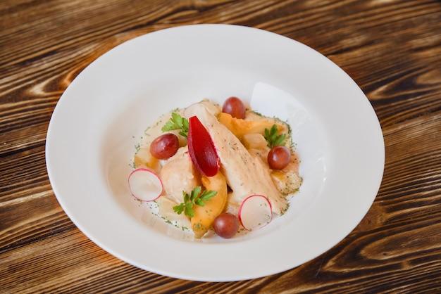 Sałatka z piersi kurczaka z melonem na białym talerzu i drewnianym stole, zdrowa dla osób kontrolujących wagę. danie z kurczaka przyozdobione winogronami, plasterkami rzodkiewki i ziołami.