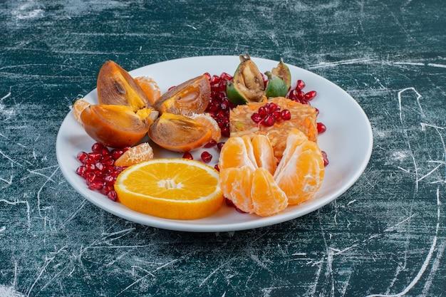 Sałatka z pokrojonych i posiekanych owoców na półmisku na niebieskiej powierzchni.