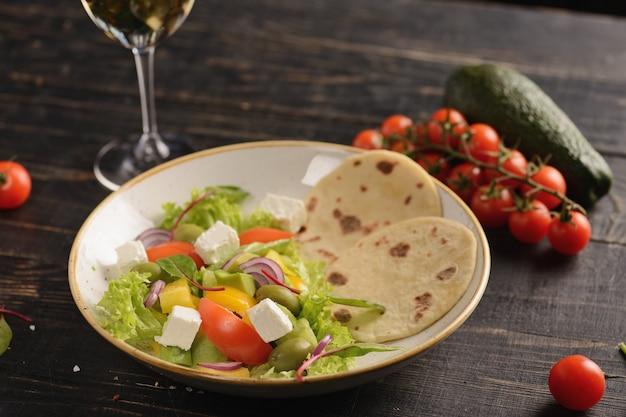 Sałatka z pomidorami, ogórkami, papryką, oliwkami i serem feta. sałatka grecka. w białej glinianej płytce na drewnianym stole