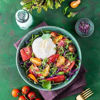 Sałatka z pomidorami, rukolą, serem burrata i microgreens na zielonym kamiennym tle, widok z góry, kwadrat