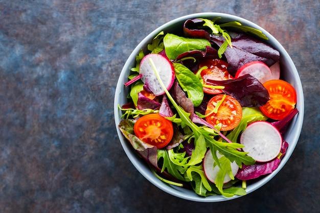 Sałatka z pomidorkami koktajlowymi, rzodkiewką i mixem sałat. zdrowa sałatka, liście mix sałat. koncepcja diety paleo. skopiuj miejsce. widok z góry