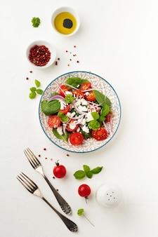 Sałatka z pomidorów, liści szpinaku, czerwonej cebuli i sera feta na jasnym talerzu ceramicznym. selektywne skupienie. widok z góry.