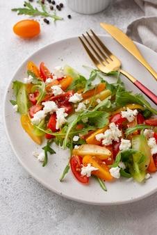 Sałatka z pomidorów pod wysokim kątem z serem feta i sztućcami