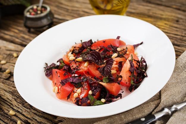 Sałatka z pomidorów z fioletową bazylią i orzeszkami piniowymi. wegańskie jedzenie. włoski posiłek.