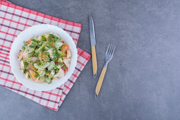 Sałatka z posiekanymi warzywami i ziołami na niebieskiej powierzchni