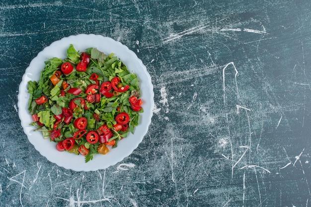 Sałatka z posiekanymi zielonymi ziołami i czerwoną papryczką chili.