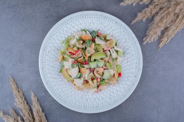 Sałatka z posiekanymi ziołami i warzywami na betonowej powierzchni