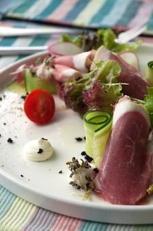 Sałatka z prosciutto i warzywami na białym talerzu w restauracji