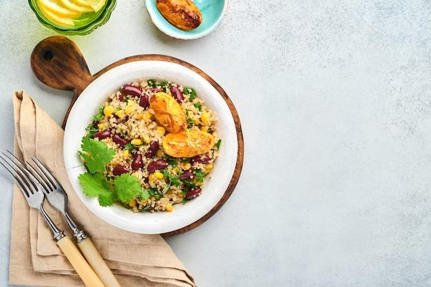 Sałatka z quinoa meksykańskiej czarnej fasoli z karmelizowaną cytryną w starej glinianej misce vintage na jasnoszarym tle betonu. tradycyjne danie kuchni meksykańskiej. widok z góry, makieta.