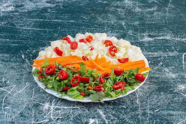 Sałatka z różnorodnymi składnikami, w tym pomidorkami koktajlowymi, ziołami i przyprawami.