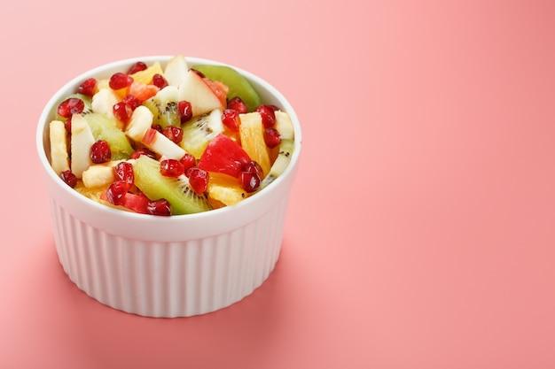 Sałatka z różnych soczystych dojrzałych owoców w białej filiżance na różowym tle. wolna przestrzeń