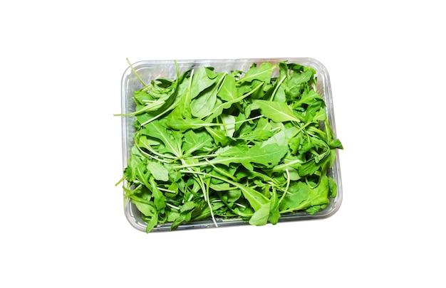 Sałatka z rukoli w plastikowym pudełku na białym tle. sałata ruccola zdrowa żywność. koncepcja wegetariańskiego stylu życia. zielone świeże witaminy.