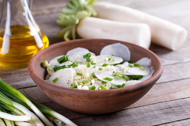 Sałatka z rzodkiewki daikon ze świeżą cebulą, pieprzem, solą morską i oliwą w misce