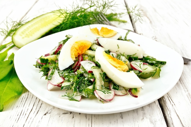 Sałatka z rzodkiewki, ogórka, szczawiu, zieleni i jajek, ubrana w majonez i śmietanę w talerzu na tle jasnych drewnianych desek