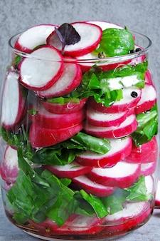 Sałatka z rzodkiewki ze szpinakiem w słoiku. sałatka fitness świeżych warzyw w słoiku. fermentacja warzyw.
