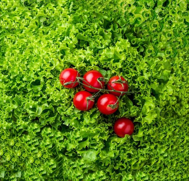 Sałatka z sałaty i czerwone pomidorki koktajlowe na szarym tle drewna