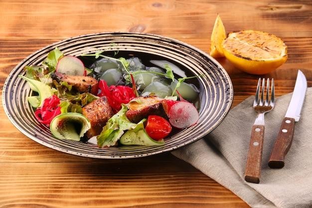 Sałatka z sandacza z warzywami w talerzu na drewnianym stole cytryna do ryb i piwa obiad